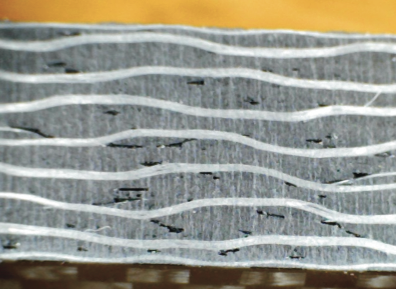 """Photo 1-Abrasive waterjet machined, 3/16"""" thick commercial carbon fiber under 30X magnification."""
