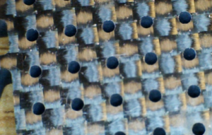"""Photo 3-1/16"""" holes pierced in 1/4"""" carbon fiber with low pressure water and abrasive."""